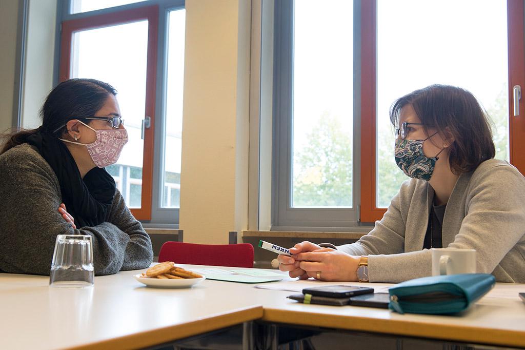 Zwei Frauen mit Nasen-Mundschutz am Tisch sitzend im Gespräch