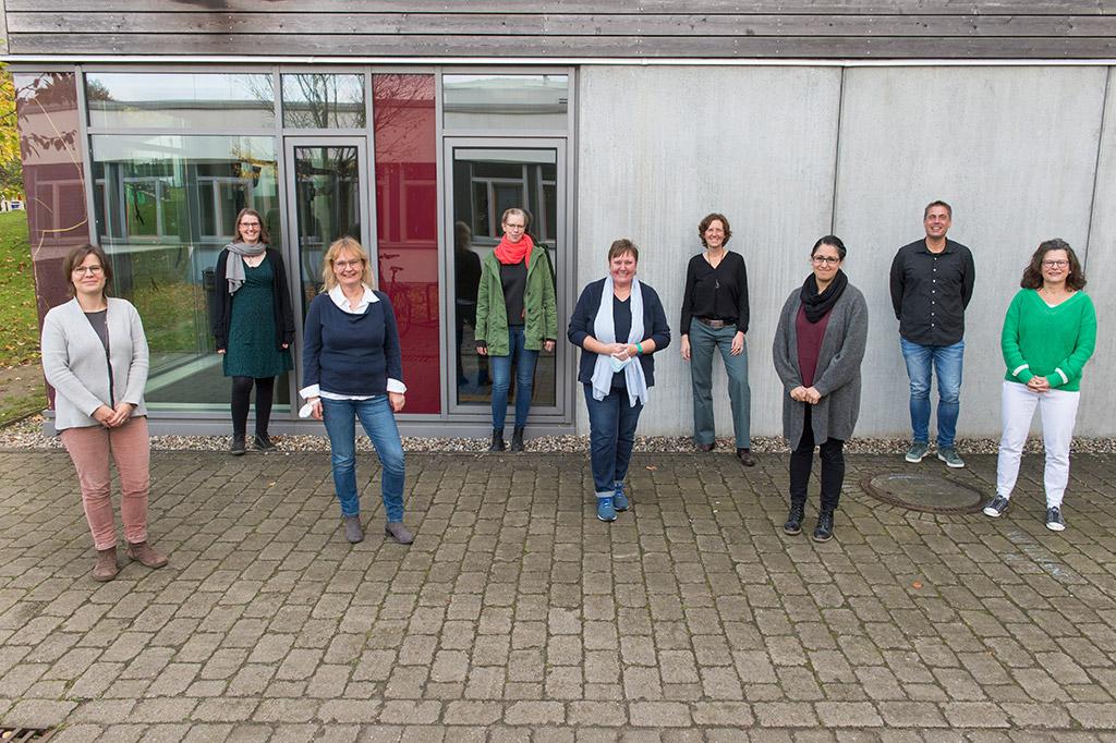 Neun Menschen stehen mit Abstand vor einem Haus