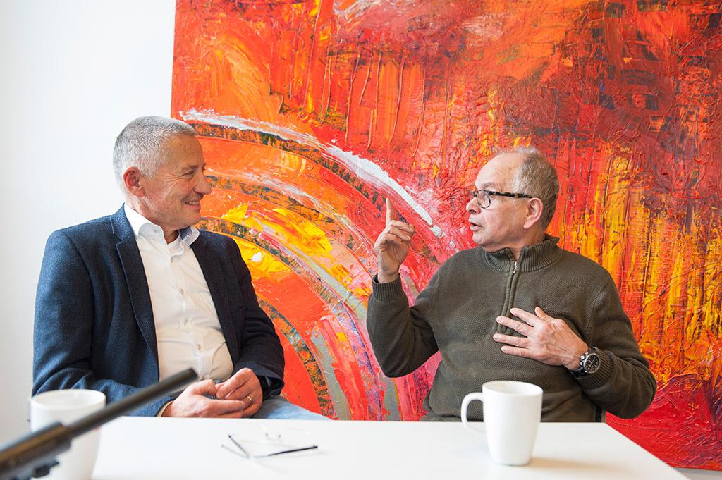 Michael Wunder und Wolfgang Masuk sitzen zugewandt an einem weißen Tisch