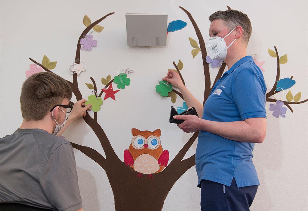 """Stationsleitung Katy Ziegler mit einem Patienten am """"Wunschbaum"""""""